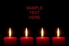 Vier rote Kerzen, schwarzer Hintergrund stockfotografie