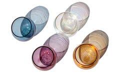 Vier runde Gläser der mehrfarbigen Weinlese auf einem weißen Hintergrund mit schönen farbigen Schatten lokalisierten im Sonnenlic lizenzfreie stockbilder