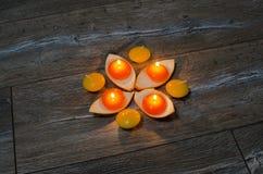 Vier runde orange Kerze, die in den Ständen des orange Pipis brennt Lizenzfreies Stockbild