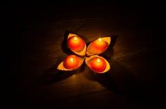 Vier runde orange Kerze, die in den Ständen des orange Pipis brennt Lizenzfreie Stockfotos