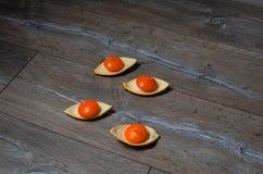 Vier runde orange Kerzen in den Ständen der orange Schale O Lizenzfreies Stockfoto