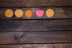 Vier runde Plätzchen und rosa Herz gemacht vom Papier Stockbild