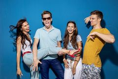 Vier schöne Freunde lachen bei der Stellung vor der blauen Wand, welche die überzeugten und glücklichen Blicke hat stockbilder