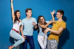Vier schöne Freunde lachen bei der Stellung vor der blauen Wand, welche die überzeugten und glücklichen Blicke hat stockfotografie