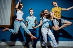 Vier schöne Freunde lachen beim Springen vor der blauen Wand, welche die überzeugten und glücklichen Blicke hat stockbilder
