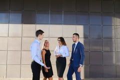 Vier schöne junge Leute, zwei Frauen und zwei Männer sprechen, rattern Stockfotografie