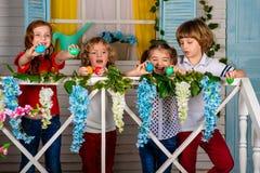 Vier schöne Kinder, zwei Jungen und zwei Mädchen stehen auf einer hölzernen Schwelle und einem Lachen stockbild