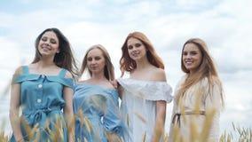 Vier schöne Mädchen auf einem Weizengebiet die Kamera aufpassend stock video footage