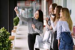 Vier schöne Mädchen, die selfie im Einkaufszentrum tun stockfotos