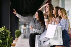 Vier schöne Mädchen, die selfie im Einkaufszentrum tun lizenzfreie stockfotos