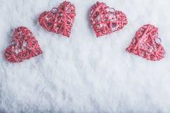 Vier schöne romantische Weinleseherzen auf einem weißen eisigen Schneehintergrund Liebe und St.-Valentinsgruß-Tageskonzept Lizenzfreies Stockfoto