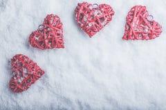 Vier schöne romantische Weinleseherzen auf einem weißen eisigen Schneehintergrund Liebe und St.-Valentinsgruß-Tageskonzept Stockfotografie