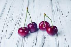 Vier schöne rote Kirschen auf einem weißen Holztisch Stockfotos