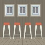 Vier Schemel-Stühle unter drei Windows Weinlese-Art Lizenzfreies Stockfoto