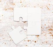 Vier schlossen weiße Puzzlespielstücke auf Tabelle an Stockbilder