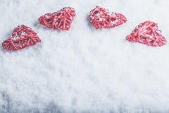 Vier schöne romantische Weinleseherzen auf einem weißen eisigen Schneehintergrund Liebe und St.-Valentinsgruß-Tageskonzept Lizenzfreie Stockfotos