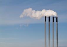 Vier schoorstenen op een blauwe hemel Stock Foto's
