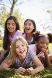 Vier Schulmädchen, die oben auf einander auf einem Gebiet, Abschluss liegen stockfotos