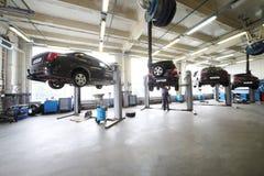 Vier schwarze Autos auf Aufzügen in der kleinen Tankstelle Stockfotos