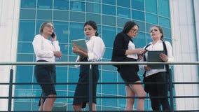 Vier slimme stads bedrijfsvrouwen die zaken in openlucht doen Zij bespreken hun projecten en plannen stock videobeelden