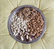 Vier soorten gepelde noten op een zilveren dienblad Okkernoten, cachou, paranoten, amandelen royalty-vrije stock afbeeldingen