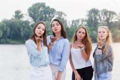 Vier speelse aantrekkelijke jonge vrouwen die en kussen bevinden verzenden zich bij camera openlucht bomen en rivier bij achtergr royalty-vrije stock fotografie