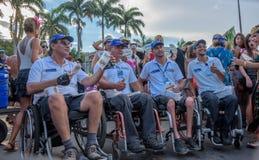 Vier sperrten Mann in verteilenden Broschüren des Rollstuhls von Lei Seca während Bloco Orquestra Voadora in Flamengo-Park, Carna Stockfotos