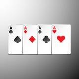 Vier Spielkarteklagensymbole auf grauem Hintergrund Stockfotografie