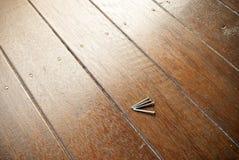 Vier spijkers op een bevlekt houtdek Stock Fotografie