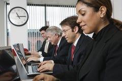 Vier stafmedewerkers die laptops met behulp van. Stock Foto