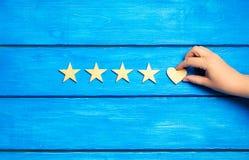 Vier Sterne und Herz auf einem blauen Hintergrund Veranschlagen von fünf Sternen, von Wahl des Redaktionsbüros und von Käufer Kon Stockbild