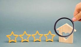Vier sterren en een blokhuis op een grijze achtergrond Succes terugkoppeling Goede evaluatie van de criticus Hotelclassificatie K royalty-vrije stock foto