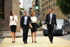 Vier succesvolle bedrijfsmensen die de straat in de stad kruisen Stock Foto