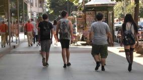 Vier Teenager, die hinunter die Straße einer Stadt mitten in den Leuten gehen lizenzfreies stockbild