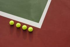 Vier Tenniskugeln auf dem Gericht Lizenzfreies Stockbild
