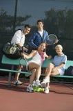 Vier Tennisspieler der gemischten Doppeln an der Bank am Tennisplatzporträt lizenzfreie stockfotografie