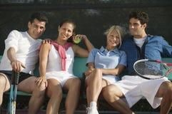 Vier Tennisspieler der gemischten Doppeln, die auf Bank am Tennisplatzporträt sitzen lizenzfreies stockfoto