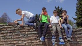 Vier tienerjaren zitten bij concrete muur in park stock footage