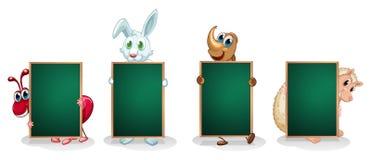 Vier Tiere mit leeren grünen Schildern Lizenzfreies Stockfoto