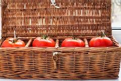 Vier Tomaten im aus Weiden geflochtenen Retro- Kasten Stockfotografie