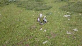 Vier Touristen, die auf einer großen grünen Lichtung am Fuß des hohen felsigen Berges sitzen, um ein Video mit einem Drohnenflieg stock footage