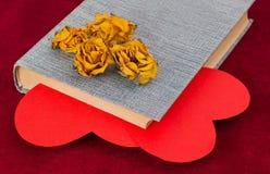 Vier trockneten die gelben Rosen, die auf dem Buch mit zwei roten Herzen liegen Stockfotos