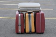 Vier uitstekende koffers op een parkeerterrein Stock Foto's