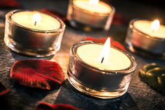 Vier Valentine Candlelights On Slate With Rose Petals And Leafs Stockfotos