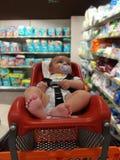 Vier van de babymaanden oud jongen in supermarkttrolli voor babyes Royalty-vrije Stock Foto's