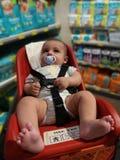 Vier van de babymaanden oud jongen in supermarkttrolli voor babyes Royalty-vrije Stock Afbeeldingen