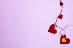 Vier in Verbindung stehende Herzen zum leichten violetten Hintergrund Lizenzfreies Stockfoto