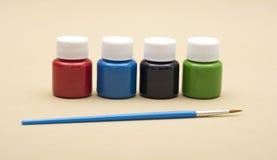 Vier verfflessen in eerste kleuren met het schilderen van borstel Stock Afbeeldingen