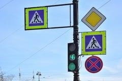 Vier Verkehrsschilder und grünes Verkehr lightagainst blauer Hintergrund, St Petersburg, Russland lizenzfreie stockbilder