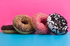 Vier verschillende donuts op blauwe en roze achtergrond royalty-vrije stock fotografie